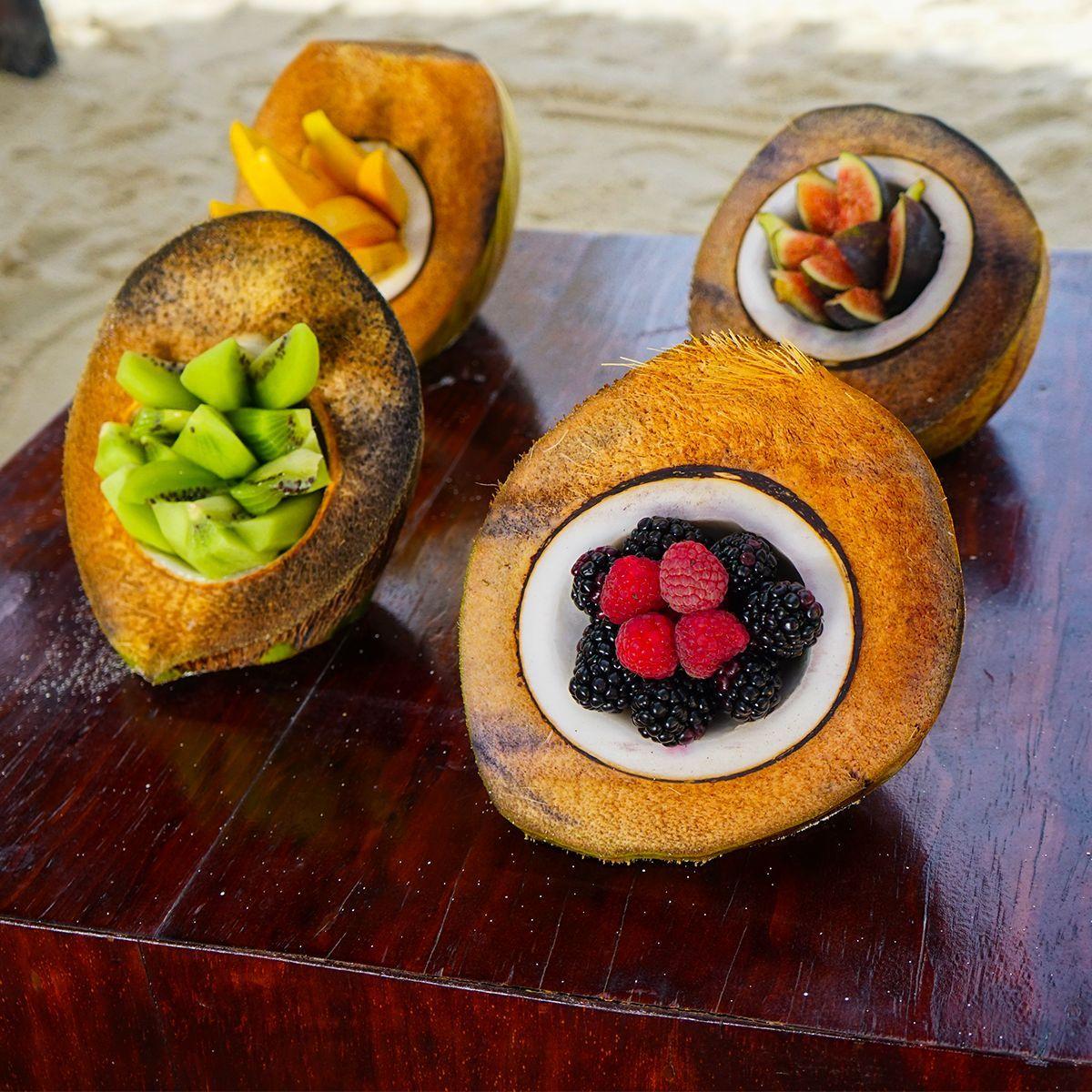 Desayunar cocos rellenos de frutas tropicales en la Riviera Maya